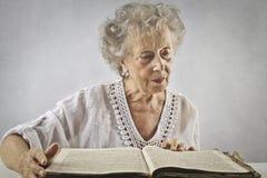 åldrig bokavläsningskvinna royaltyfria bilder