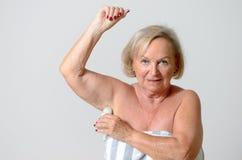 Åldrig dam Applying Deodorant för mitt på armhålan Royaltyfri Bild