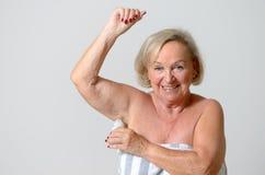 Åldrig dam Applying Deodorant för mitt på armhålan Arkivfoto