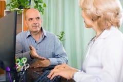 Åldrig doktor som talar med den mogna manliga patienten Arkivfoto