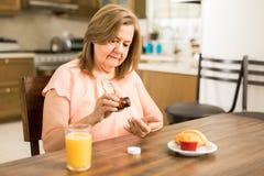Åldrig farmor som tar medicin för att behandla hennes sjukdom royaltyfri foto