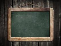 Åldrig grön blackboard som hänger på träväggen Arkivfoto
