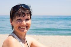 Åldrig kvinna för lycklig mitt på stranden Royaltyfria Bilder