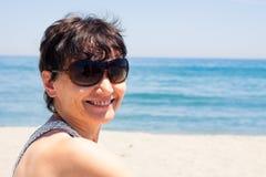 Åldrig kvinna för lycklig mitt på stranden Arkivbilder