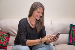 Åldrig kvinna för mitt med en mobiltelefon Royaltyfri Bild