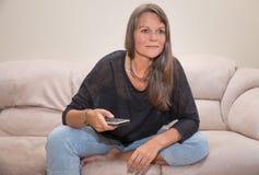 Åldrig kvinna för mitt med en tvfjärrkontroll Arkivfoton