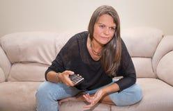 Åldrig kvinna för mitt med en tvfjärrkontroll Royaltyfri Fotografi