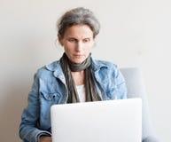 Åldrig kvinna för mitt som använder datoren Royaltyfri Bild