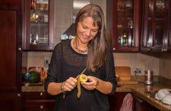 Åldrig kvinna för mitt som klipper en kiwi Royaltyfri Fotografi
