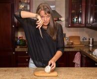 Åldrig kvinna för mitt som klipper en vit lök Arkivfoto