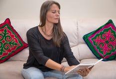 Åldrig kvinna för mitt som läser en bok Arkivfoton