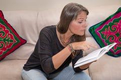 Åldrig kvinna för mitt som läser en bok Royaltyfria Bilder