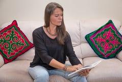 Åldrig kvinna för mitt som läser en bok Arkivfoto