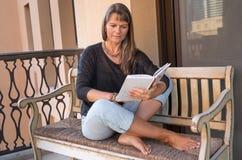 Åldrig kvinna för mitt som läser en bok Royaltyfria Foton