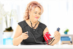Åldrig kvinna för mitt som mäter blodtryck, hemma Fotografering för Bildbyråer