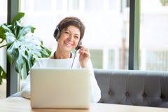 Åldrig kvinna i hörlurar med mikrofon och bärbar dator på tabellen royaltyfri bild