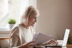 Åldrig kvinna som är upptagen med dokument som arbetar på bärbara datorn royaltyfri foto