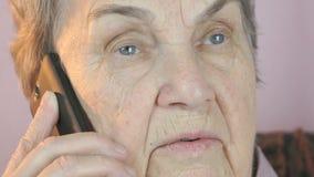Åldrig kvinna som allvarligt talar på den mobila smartphonen lager videofilmer