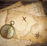 Åldrig mässingsnautisk kompass på tabellen med gamla översikter Arkivfoto