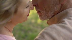 Åldrig make och fru som kysser closeupen, förälskelse som känner sig, gift parsamhörighetskänsla royaltyfria bilder