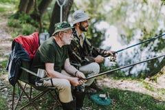 Åldrig man som fiskar med hans son på flodbanken arkivbild