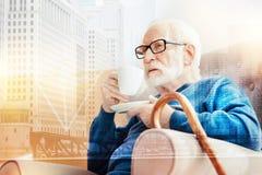 Åldrig man som rynkar pannan, medan sitta i hans fåtölj och dricka kaffe Royaltyfri Bild