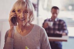 Åldrig sällskaplig kvinna som ler och har konversation arkivfoton