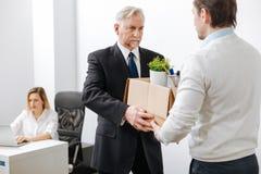 Åldrig skäggig arbetsgivare som ger asken till anställd royaltyfria foton