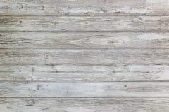 Åldrig yttersida av horisontalträplankor med sprucken vit målarfärg Skalning av målarfärg på en gammal trävägg arkivfoto