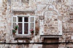 Åldriga fönster och blommaaskar av historisk byggnad från gammal stad av Pula, Kroatien/detalj av forntida venetian arkitektur Royaltyfri Bild