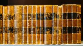 Åldriga forntida antika gamla tappningböcker på en Shelfs i arkiv Royaltyfria Foton