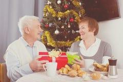 Åldriga par som utbyter gåvor Arkivbild