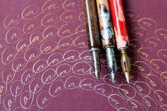 Åldriga reservoarpennor, konstnärlig ram med bokstäver A OrdCalligraphique begrepp bronssilverfärgpulver pink för bakgrundspapper Arkivfoto
