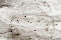 Åldrigt pappers- ark, smutsfläckar, fläckar, skrynkla, grungetappningbakgrund fotografering för bildbyråer