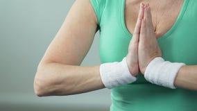 Åldrigt sätta för kvinnlig gömma i handflatan en mot andra i yogalotusblommapositionen, hobby stock video