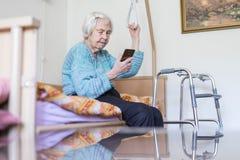 Åldring 96 år för läsningtelefon för gammal kvinna meddelande, medan sitta på medicinsk säng som stöttar henne vid hållaren royaltyfria foton