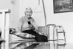 Åldring 96 år fungerande TV för gammal kvinna eller DVD med fjärrkontroll arkivfoto