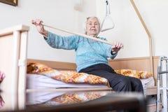 Åldring 96 år gammal kvinna som övar med en pinne som sitter på hennes dåligt arkivbilder