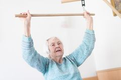 Åldring 96 år gammal kvinna som övar med en pinne som sitter på hennes dåligt arkivfoton