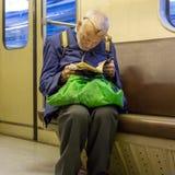 Åldring fattig ensam man i brutna exponeringsglas som läser entusiastiskt en söndersliten bok arkivfoton