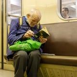 Åldring fattig ensam man i brutna exponeringsglas som läser entusiastiskt en söndersliten bok arkivbilder