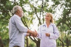 Åldring och doktor som talar om vård- sjukvårdkonsulent i en parkera royaltyfria foton
