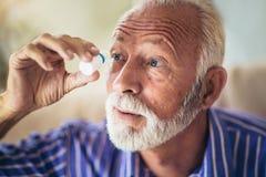 Åldring Person Using Eye Drops arkivbilder