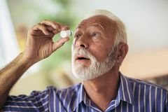 Åldring Person Using Eye Drops arkivbild