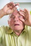 Åldring Person Using Eye Drops Arkivfoto