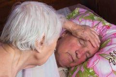 Åldring 80 plus årig man i en hemsäng royaltyfria foton