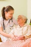 åldring som hjälper den sjuka kvinnan Royaltyfria Bilder