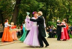 Åldringen ångar i bolldräkter dansar på stadsfyrkant Arkivfoton