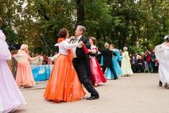 Åldringen ångar i bolldräkter dansar på stadsfyrkant Royaltyfri Fotografi