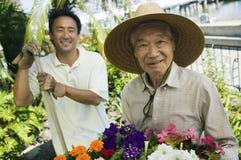 Åldringen bemannar med sonen i trädgård Royaltyfri Fotografi